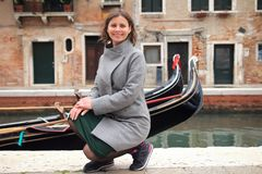 Woman in Venice, Italy. Cute smiling girl on venetian canal with gondolas. Happy young woman in Venice stock photos
