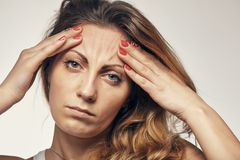 Woman is very worried about her beauty. A young woman is very worried about her beauty Royalty Free Stock Image