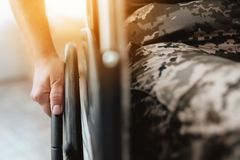 Woman veteran in wheelchair returned from army. Close-up photo veteran woman in a wheelchair. Wheelchairs and legs in military uniform royalty free stock photos