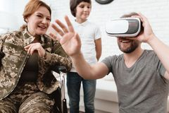 Woman veteran in wheelchair returned from army. A man looks into virtual reality glasses. Woman veteran in wheelchair returned from army. A men looks into Royalty Free Stock Images