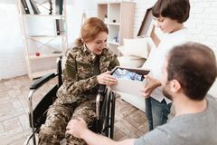 Woman veteran in wheelchair returned from army. The son and husband are happy to see her. Men give a gift to a women in a wheelchair royalty free stock image