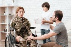Woman veteran in wheelchair returned from army. The son and husband are happy to see her. Royalty Free Stock Images