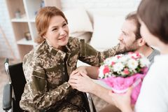 Woman veteran in wheelchair returned from army. The son and husband are happy to see her. Men give a women in a wheelchair bouquet of flowers royalty free stock images
