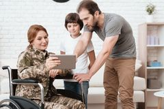 Woman veteran in wheelchair returned from army. The son and husband are happy to see her. A women in a wheelchair shows her son and husband something on the Stock Photography