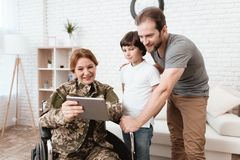 Woman veteran in wheelchair returned from army. The son and husband are happy to see her. A women in a wheelchair shows her son and husband something on the Royalty Free Stock Photo