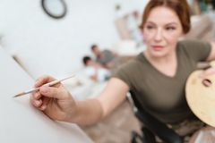 Woman veteran in wheelchair returned from army. A woman in a wheelchair draws on canvas. Stock Photography