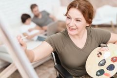 Woman veteran in wheelchair returned from army. A woman in a wheelchair draws on canvas. Stock Image