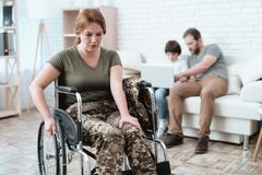 Woman veteran in wheelchair returned from army. A woman in a wheelchair is in pain. She`s in military uniform. Woman veteran in wheelchair returned from army. A royalty free stock photo
