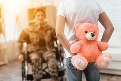 Woman veteran in wheelchair returned home. The son is happy to see his mother after returning from the army. The son gives his mother in a wheelchair a teddy royalty free stock images