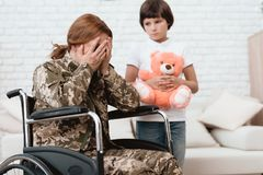 Woman veteran in wheelchair returned home. The son is happy to see his mother after returning from the army. The son gives his mother in a wheelchair a teddy royalty free stock photo