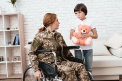 Woman veteran in wheelchair returned home. The son is happy to see his mother after returning from the army. The son gives his mother in a wheelchair a teddy stock photos