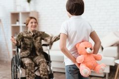Woman veteran in wheelchair returned home. The son is happy to see his mother after returning from the army. The son gives his mother in a wheelchair a teddy stock photo