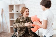 Woman veteran in wheelchair returned home. The son is happy to see his mother after returning from the army. The son gives his mother in a wheelchair a teddy stock photography