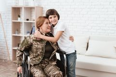Woman veteran in wheelchair returned home. Son hugs mom in wheelchair. Woman veteran in wheelchair returned home. The son is happy to see his mother after Royalty Free Stock Image