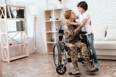 Woman veteran in wheelchair returned home. Son hugs mom in wheelchair. Woman veteran in wheelchair returned home. The son is happy to see his mother after Stock Image