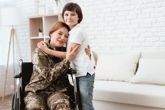 Woman veteran in wheelchair returned home. Son hugs mom in wheelchair. Woman veteran in wheelchair returned home. The son is happy to see his mother after Royalty Free Stock Photography