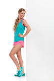 Woman In Vibrant Sport Clothes Leaning Against Banner. Smiling beautiful young woman in pink shorts, turquoise tank top and sneakers standing and leaning against stock images
