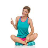Woman In Vibrant Sports Clothes Showing Thumb Up. Beautiful smiling young woman in vibrant sports clothes sitting on a floor with legs crossed, showing like hand Stock Photography