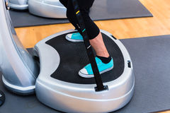 Woman on vibrating plates in gym training Stock Photography