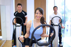 Woman on vibration plate in a gym. Group of two men and one women on a vibration massage plate in a gym Royalty Free Stock Photo