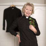 Woman vicar holding a sprig of Holly Royalty Free Stock Image