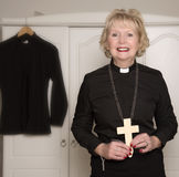 Woman vicar holding a wooden cross Royalty Free Stock Photography