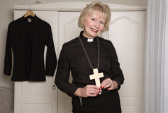 Woman vicar holding a wooden cross Royalty Free Stock Image