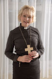 Woman vicar holding a wooden cross Royalty Free Stock Images