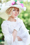 Woman in victorian age. Portrait of beautiful woman in victorian age dress and fancy hat with flowers Stock Photos