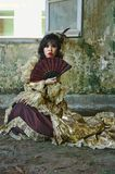 Woman in Victorian Costume. Chinese woman wearing victorian costume holding a fan, shoot at grunge building royalty free stock image