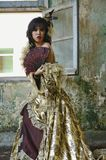 Woman in Victorian Costume. Chinese woman wearing victorian costume holding a fan, shoot at grunge building royalty free stock photos