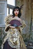 Woman in Victorian Costume. Chinese woman wearing victorian costume holding a fan, shoot at grunge building stock photo