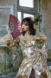 Woman in Victorian Costume. Chinese woman wearing victorian costume holding a fan, shoot at grunge building stock image