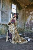 Woman in Victorian Costume. Chinese woman wearing victorian costume holding a fan, shoot at grunge building stock photos