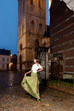 Woman in Victorian dress in the city. Woman in Victorian dress in the historic city of Leuven with medieval church and antique houses royalty free stock photo