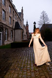 Woman in Victorian dress, old city square, evening. Girl in a white Victorian dress dancing in the historic city of Leuven with medieval church and antique royalty free stock photo