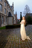 Woman in Victorian dress in a old city square in the evening in profile Stock Images