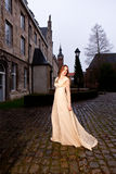 Woman in Victorian dress in a old city square in the evening walking. Woman in a white Victorian dress walking in the historic city of Leuven with medieval stock photos