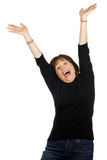 Woman in victorious expression. Middle aged confident woman expressing a joyous and victorious moment with arms raised in the air Royalty Free Stock Photos