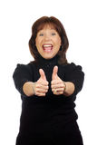 Woman in victorious expression with thumbs raised. Middle aged confident woman expressing a joyous and victorious moment with thumbs up for the win or success Royalty Free Stock Photo