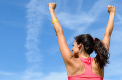 Woman victory. Woman from behind with arms raised expressing success towards sky on a sunny summer day Royalty Free Stock Images