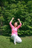 Woman in victory pose. A woman raises her hands in a victory pose while squatting in a park Royalty Free Stock Photo