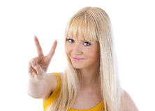 Woman with victory sign. Cheerful young woman showing victory sign over white Royalty Free Stock Photo