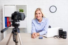 Woman video blogger talking about photography and videography. Young woman video blogger talking about photography and videography stock image