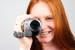 Woman with Video Camera. A young woman shooting video with an amateur camera on plain background - closeup image Stock Photos