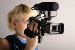 Woman with video camera. Young blond woman hold professional video camera Royalty Free Stock Images