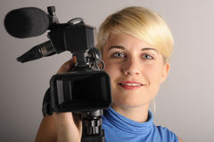 Woman with video camera. Portrait blond friendly woman with video camera in hand Stock Photo