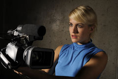 Woman with video camera. Young blond nice woman hold video camera Royalty Free Stock Photo