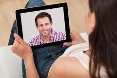 Woman video chatting with man. High angle view of young women video chatting with men at home royalty free stock image