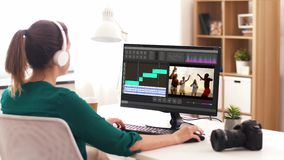 Woman with video editor program on computer. Technology, post production and vlog concept - woman in headphones working on video of summer vacation in editor stock footage